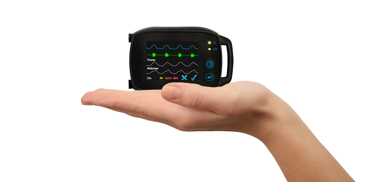A picture of a small compact SOMNOtouch PSG, polysomnography Sleep diagnostic device being held in a hand to show how small it is. The device can also be used on its own with a head box meaning the patient is free to move around at anytime.