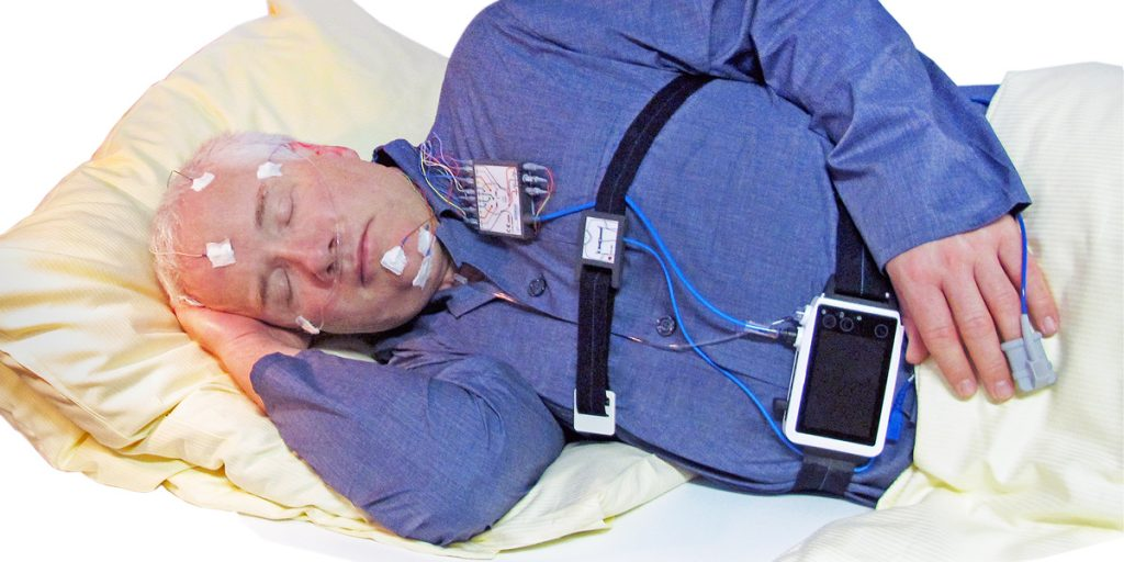 A patient wearing a SOMNOscreen HD PSG device - highlighting how small and mobile it is.