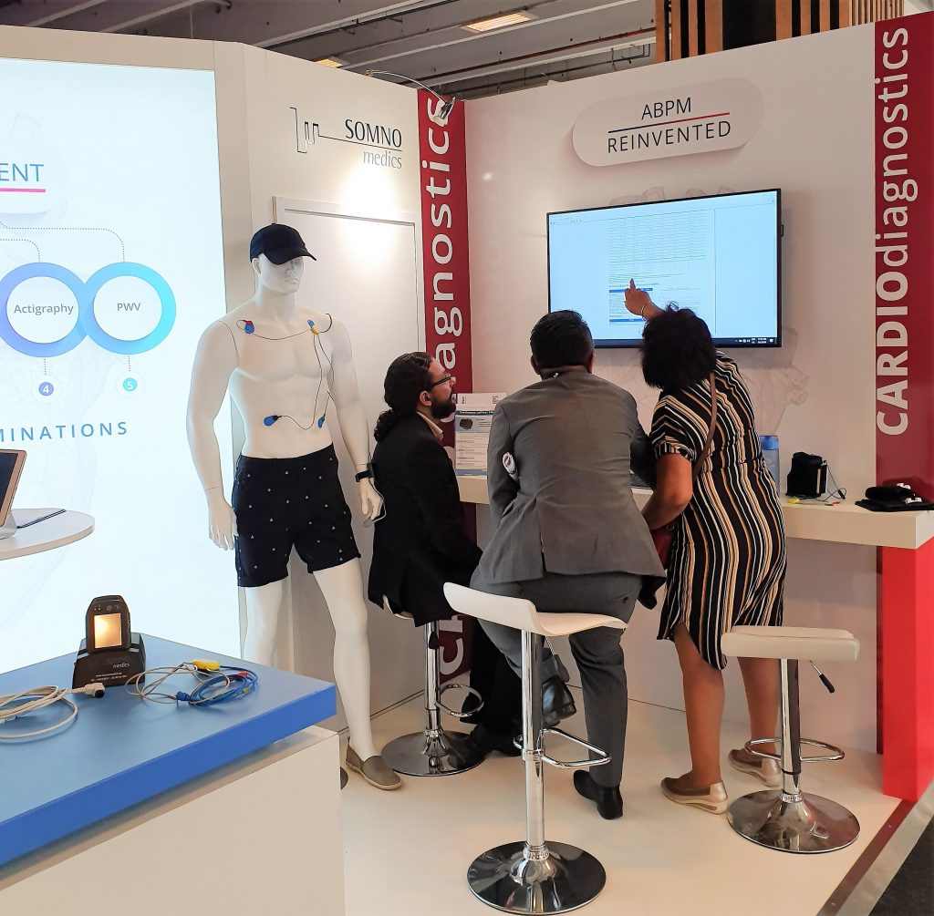 Doctors at our booth F110 being shown the 24 hour beat-to-beat blood pressure report generated from the SOMNOtouch NIBP device.